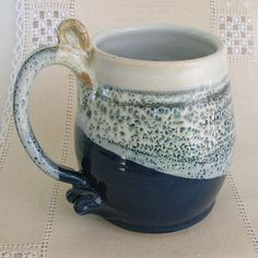 This classic, navy and white, stoneware, pottery beer stein has a handle that fits a full fingered grip. Where the two glazes (navy and white) meet