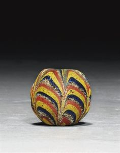 EARLY ISLAMIC LARGE MARVERED GLASS BEAD  SYRIA OR EGYPT, 9TH CENTURY  Of spherical form, the body composed of swagged bands of cobalt-blue, yellow, light red and white glass, the white glass very pitted, drilled through centre 1½in. (3.7cm.) high .