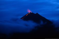 Arenal volcano, covered in a shroud of clouds, erupts at night in La Fortuna, Alajuela, Costa Rica.