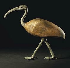 AN EGYPTIAN BRONZE AND GILT WOOD IBIS   LATE PERIOD TO PTOLEMAIC PERIOD, CIRCA 664-30 B.C.   Striding forward with left leg advanced, with incised details of the scales along the legs and the joints of the feet, the S-shaped neck and long bill curved, the round eyes inlaid with glass, bulging beneath ridged brows, the wood body gilt, the bronze tail with incised feather detail  13 in. (33 cm.) high