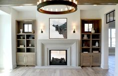 Illuminated by a Ralph Lauren Roark Modular Ring Chandelier, this stunning living room features a blue and gray abstract art piece mounted between Square Tube Single Sconces above a limestone fireplace flanked by gray wash bookcases placed in alcoves.