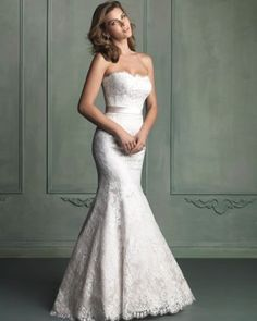 A thick satin sash adds dramatic sophistication to this strapless satin gown with an all-over lace overlay.