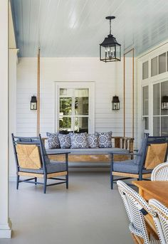 White and blue covered patio features a blue beadboard ceiling accented with a rope and salvaged wood swinging sofa lined with blue pillows facing a pair of seagrass chairs painted blue.