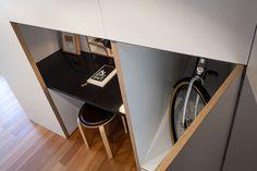 ロフトベッドルーム付きのゆったりとしたワンルームの入り口脇のワークスペースとその横の自転車収納クローゼット