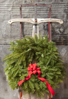 hanging a wreath from a sled, clever and cute idea for a front porch.