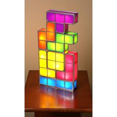 """TETRIS LAMP Plug in the blue four-cube base, and start to play. Pile up these individual Tetris elements and they illuminate as soon as they come in contact with each other, so you can create an infinite number of combinations; remove a piece, and its light turns off. UL listed. Seven plastic-andmetal pieces. Base is 6½""""."""