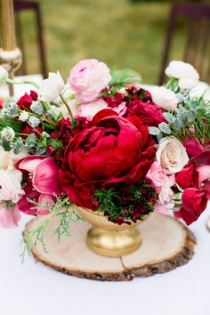 Gorgeous cranberry Peony arrangement in an elegant gold urn, set atop a rustic wood round. #wedding #flowers