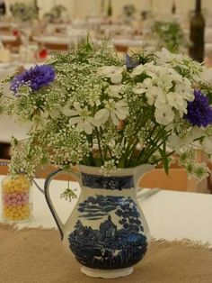 Blue and white jug filled with blue cornflower, white orlaya, nigella, sweetwilliams and ammi