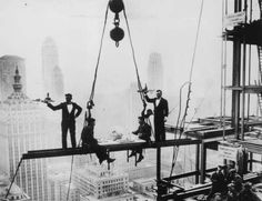 Two waiters serve two steel workers lunch, on a girder high above New York City, 14th November 1930.... - Photo by Keystone/Getty Images