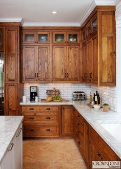 LOVE the wood grain cabinets, and how the light backsplash and counters brighten the room and provide relief from the wood.  This is a gorgeous kitchen.