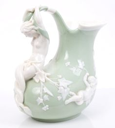 Victorian Minton green and white glazed ewer after the antique, with mermaid handle and demon mask and putti decoration - incised marks, 19cm