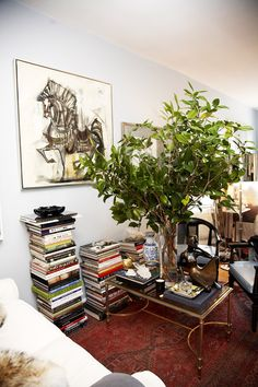 Though interior designer Ryan Korban's stacks of art and design books aren't organized by color, piling up like-sized books and topping them with accessories, ashtrays, and crystal gives them polish. Source