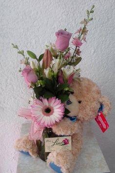 Muñeco de peluche con un arreglo floral.