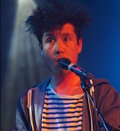 Dan Smith of Bastille, in a hoodie and his blue striped shirt, singing, with wild hair