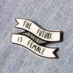 """Turn any outfit into a feminist's outfit with this unique lapel pin. It features the quote, """"The future is female"""" on a black and white banner. Perfect for use on a jacket, bag, scarf, and more. This"""