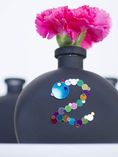 Our slender half-round Chalkboard Vase bottles are as versatile as they are fashionable. Here, metallic confetti is used to scribe a table number for a reception table. Use small bits of office poster putty for an easy-to-clean option!