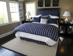 Near black hardwood floor grounds this bedroom featuring China-patterned curtains and pillows, mirrored bedside tables, and navy blue cloth surfaces.