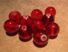 Punaisia ja/tai liiloja lasihelmiä, tällaisia tai vastaavia.