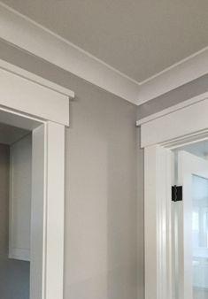 Modern craftsman woodwork in the molding around the doors. Soft gray walls, white trim