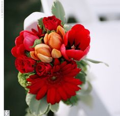Small bouquets of gerbera daisies, tulips, and roses were hanging from the end chair in every other row, lining the aisle at the ceremony.
