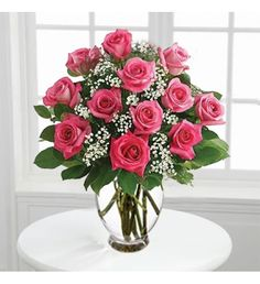 Floral bouquet/arrangement with long-stem pink roses and arrange them by hand with fresh gypsophila in a classic glass vase. Available in bouquets of 12 stems and 18 stems.