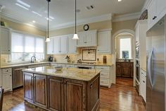 27 Creekside Ct. Gourmet kitchen features gleaming hardwood floors, beautiful wood cabinetry, under cabinet lighting, large center island, gorgeous granite counter tops, crown molding, pendant lights, recessed lighting and built-in speakers!  Bernstein Realty, Houston Real Estate.