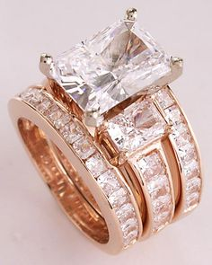 Stunning 3pc wedding set w/ 4 carat cz center and channel set princess cut cubic zirconias all set in 14k rose (pink) gold.  The engagement ring is available with the center stone & carat weight of your choice, in 14k or platinum, from Orleansjewels.com