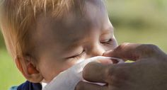 mano de la mamá limpiándole la nariz a un bebé