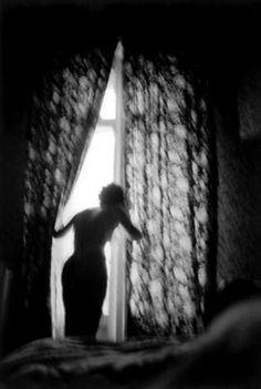 Woman looking out of hotel bedroom window, Pau, France by Erich Hartmann