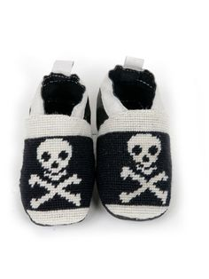 Jolly Roger Needlepoint Bab y Shoes: Available in two sizes. Size  0-6 months have a 4.5 inch sole and size 6-12 months have a 5 inch soft kid leather sole.  The leather band is lined with elastic to keep them from falling off little feet. The soles are very soft kid leather and highly recommended by pediatricians.  These booties are designed in house and stitched by hand.  So popular, they are the only needlepoint booties available.   A perfect choice for all Hip Rock Star Babies ! Each…