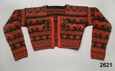 Kvinnotröja, midjekort, slätstickad i hårt tvinnat ullgarn, helt mönstrad i rött som dominant färg, samt grönt och svart. Mönstret är specifikt för socknarna Delsbo och Bjuråker. Stickningen utförd