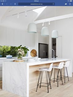 timber flooring Kitchen with pitched cathedral ceiling and exposed beams. A trio of large pendant lights hang over the white marble kitchen island. The glass splashback welcomes the outdoors in, and white cabinetry pairs with pale blonde timber flooring. Kitchen Inspirations, Interior Design Kitchen, Home Decor Kitchen, New Kitchen, Kitchen Interior, Marble Kitchen Island, Kitchen Marble, Kitchen Remodel, Kitchen Renovation