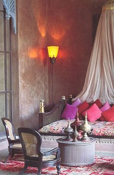 Moroccan inspired room. Love the pairing of soft, fluid fabric with ornate metal urns.