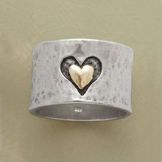 "HEART AND SOUL RING -- A heart and soul band ring, marrying precious metals and textures, with a heart hand cast into our 1/2""-wide hammered sterling band framing another of smoothly finished 14kt gold. A Sundance exclusive in whole and half sizes 5 to 9-1/2."