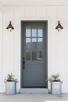 Farmhouse front door with zinc planters. Farmhouse with board and batten siding, grey front door with zinc planters. Farmhouse front door with zinc planters Millhaven Homes Painted Exterior Doors, Exterior Door Colors, Design Exterior, Painted Front Doors, Door Design, Exterior House Lights, Modern Exterior Doors, Exterior Signage, Gray Front Door Colors