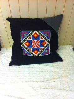 This pillow is made from an old embrodied pillow I made in the 60`s. We call it aakleembroderi. Typical norwegian. I bougt an innerpillow 60x60 and have used woolmaterial to frame the pillow. The grey corner and the grey backside make a more soft impression.