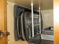 I got this idea of using curtain spring tension rods for baking pan storage from the Martha Stewart website. It works great! I can't believe how much more room I have in this cabinet. Simple, inexpensive and it won't damage the inside of the cabinet. Perfect if you are renting.