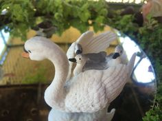 Miniature Fairy Garden - MIRROR, MIRROR IN MY HAND, WHO IS THE FAIREST IN THE LAND? has a lake and in the lake the white swan with three babies on her back and the green turtle with the baby turtle on its back gravitate toward the younger fairy. 8/2015