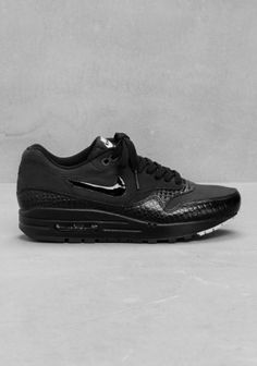 NIKE Retro style sneakers featuring a matte nubuck upper and sculpted leather detailing.