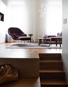 Plum accents, including a Saarinen Womb chair in aubergine Rivington fabric by KnollTextiles, complement the apartment's exposed brick. The trio of Paper tables, designed by GamFratesi for Gubi, can nest in various formations, while a Clear Ice chandelier from ABC Carpet & Home and semisheer curtains made by Beckenstein Fabric & Interiors lend the room a soft glow.