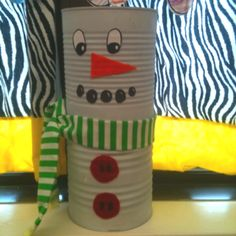 Coffee can snowman. Spray paint cans white. Hot glue together. Scarf made from fabric remnants and ribbon. Felt buttons and carrot. Drawn eyes and coal pieces with sharpie.