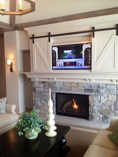 TV-above-the-fireplace-with-miniature-small-barn-doors.