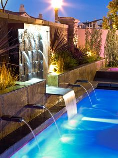 This custom pool fountain was designed using V-tile Island stone to create a beautiful waterfall effect. Lush landscaping creates a relaxing tropical space.