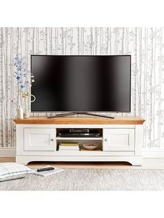 Ideal Home Wiltshire 2 Door TV Unit in Cream/Oak-Effect - suitable for televisions up to 56 inch The Wiltshire TV unit from Ideal Home has been traditionally designed with a chunky style, shaped plinth and top, panelled doors and dainty metal handles.Its softcream hue is offset by a rustic oak-effect top, which is carefully detailed with intricate grain patterns and fine 'cracks' for added character - just like you'd find on the real thing.Store your favouritefilm and TV bo...