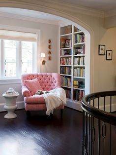tho I'm not fond of the pinkish chair, I love the reading nook, the arch of the wall, the dark wood floors - all so inviting!