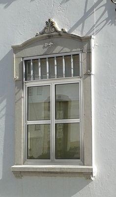 Ventana con reflejo de puerta con arquitectura típica del Algarve, Portugal