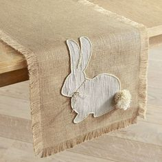 Our naturally cute jute table runner features lovely fringed edges and an appliqued bunny with the fluffiest pompom tail we've ever seen.
