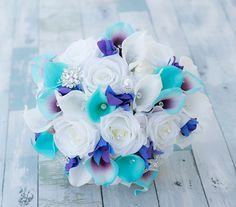 This is a beautiful -almost fresh- Aqua Turquoise Teal Mix Calla Lilies, White Roses and Blue Purple Orchids Real Touch Wedding Bouquet, made with the most realistic silk flowers available. We have added crystal and silver starfish for striking tropical themed wedding. You can get this bouquet in 10, 11, or 12 Wide. The picture shows the 12 Wide version. For the Ribbon choices, the sky is the limit! Send us a picture of your colors and well match is as close as possible. For more matching…