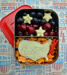 In this bento: Black grapes, cherries, yogurt covered star cookies, United States shaped cream cheese and strawberry jelly sandwich, and star cheese crackers.