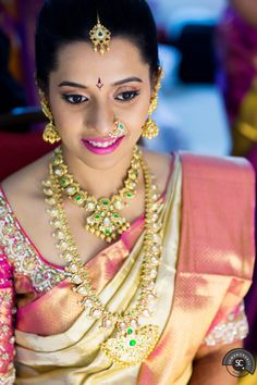 South Indian bride. Gold Indian bridal jewelry.Temple jewelry. Jhumkis.Cream silk kanchipuram sari with contrast pink blouse.braid with fresh jasmine flowers. Tamil bride. Telugu bride. Kannada bride. Hindu bride. Malayalee bride.Kerala bride.South Indian wedding.